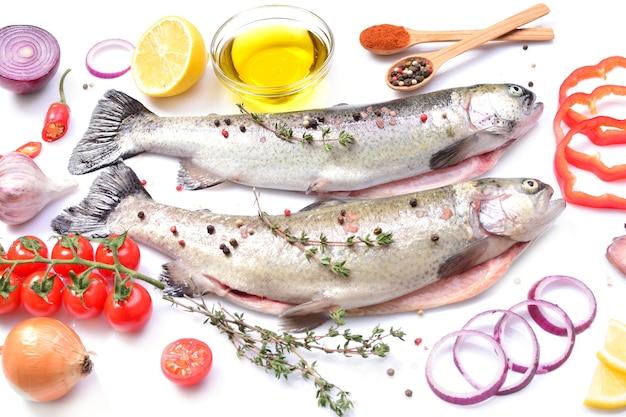 Peixe truta com especiarias e vegetais em um fundo branco