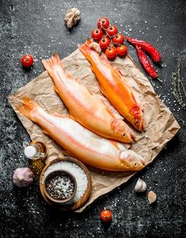 Peixe truta crua no papel com tomate, pimenta e especiarias. em rústico escuro