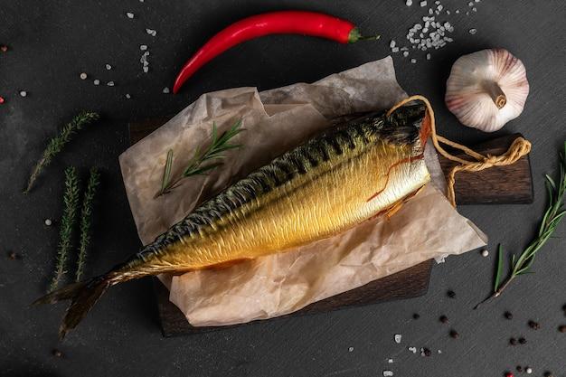 Peixe truta dourada defumada com vegetais em uma vista de cima da superfície preta, conceito de mercado de peixes