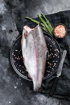 Peixe truta inteira crua sem cabeça, com sal e alecrim