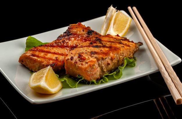 Peixe, truta, salmão amigo, jubarte, um pedaço assado, grelhado, com uma rodela de limão e alface