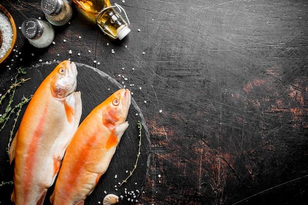Peixe truta vermelha crua com especiarias. em rústico escuro