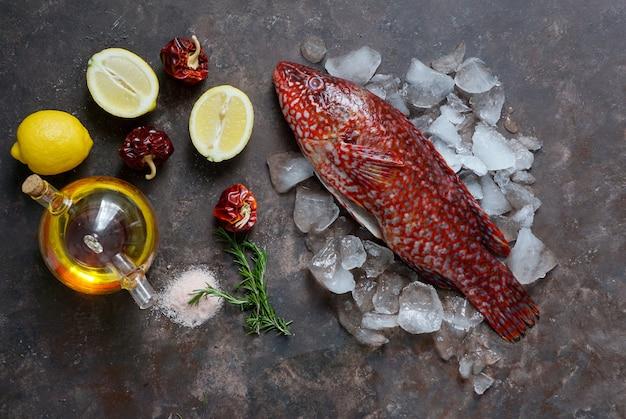 Peixe vermelho, ballan wrasse cru fresco pronto para ser cozido, vista superior, azeite, especiarias