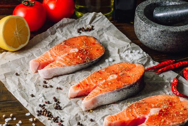 Peixe vermelho cru e algumas especiarias em papel pergaminho