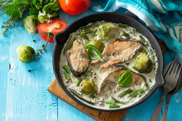 Peixe vermelho e legumes cozidos em uma frigideira com couve de bruxelas e feijão verde com molho de natas