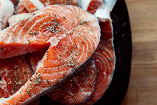 Peixe vermelho fatiado em um prato cozinhando frutos do mar com fundo de madeira