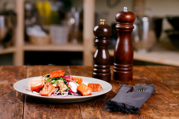 Peixe vermelho salmão com rabanete e espinafre, servido na chapa branca na mesa de madeira. estilo rústico. vista de cima, foto principal do estúdio