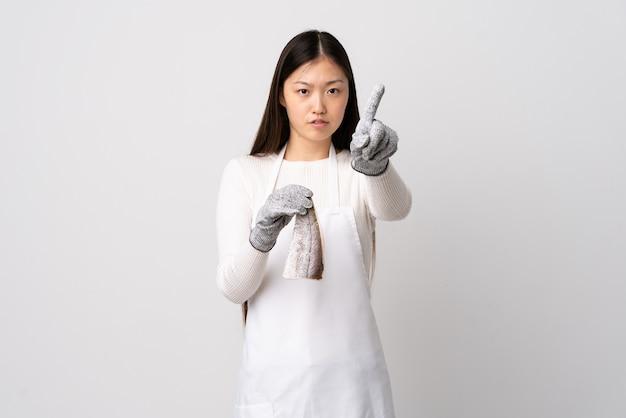 Peixeiro chinês de avental segurando um peixe cru sobre um fundo branco isolado e contando um com expressão séria