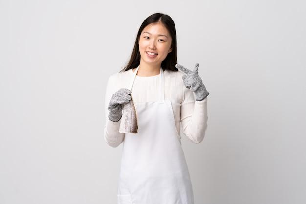 Peixeiro chinês vestindo um avental e segurando um peixe cru sobre branco isolado, dando um polegar para cima gesto