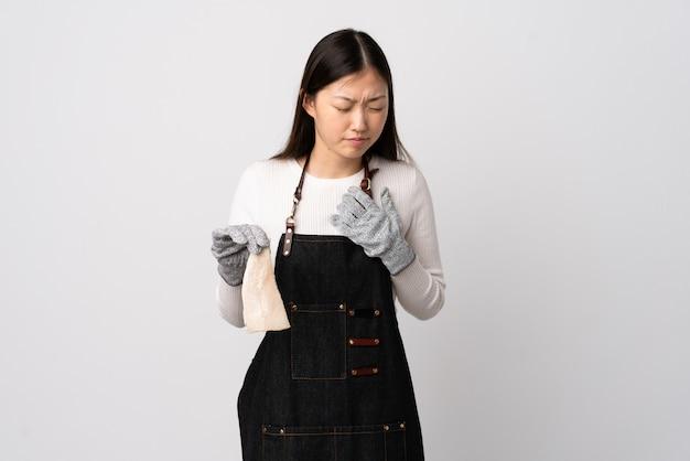 Peixeiro chinês vestindo um avental e segurando um peixe cru sobre parede branca com uma dor no coração
