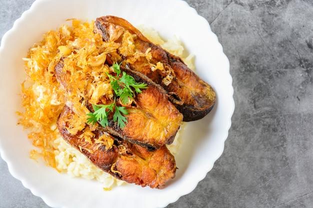 Peixes cortados fritados de pangasius com o alho, servido com arroz integral.