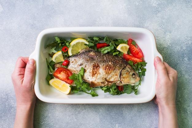 Peixes cozidos da carpa com vegetais e especiarias em uma bandeja do cozimento com espaço da cópia.