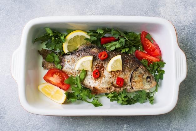 Peixes cozidos da carpa com vegetais e especiarias em uma bandeja do cozimento.