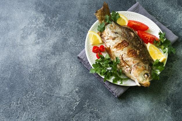 Peixes cozidos da carpa com vegetais e especiarias em uma placa em uma tabela escura com uma cópia do espaço.