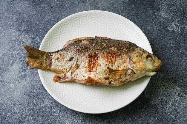 Peixes cozidos da carpa em uma placa. fundo escuro. copie o espaço.