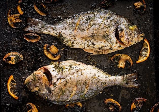 Peixes cozidos do dorado no molho do aneto do alho com cogumelos e limão.