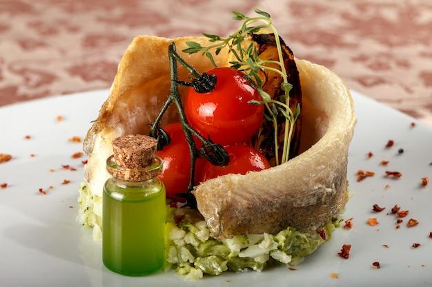 Peixes cozidos em um prato lateral vegetal com tomates de cereja.