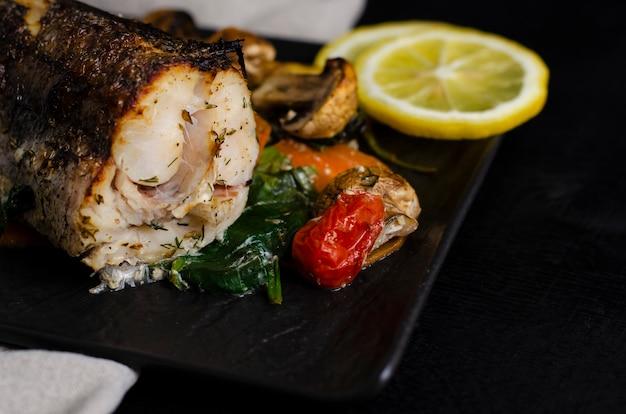Peixes cozidos grelhados ou do forno das pescadas na placa preta.