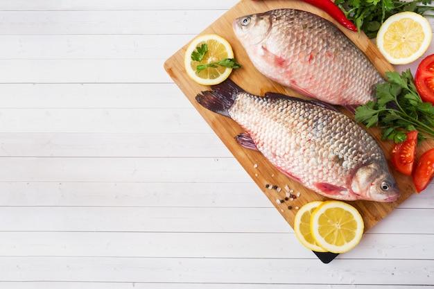 Peixes crus da carpa com especiarias e vegetais para cozinhar. a vista do topo. copie o espaço.