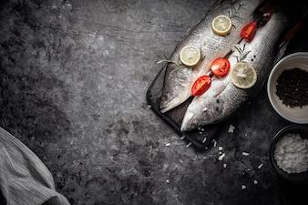 Peixes crus frescos do badejo na placa de corte de madeira, cozinhando o conceito.