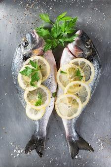 Peixes crus frescos do sargo decorados com fatias, ervas e salsa do limão no fundo claro.