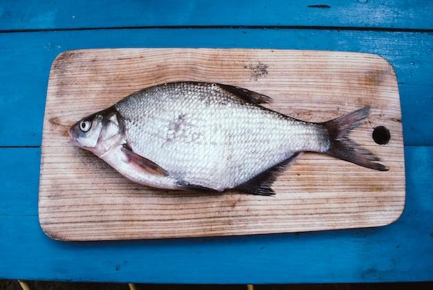 Peixes da brema em uma placa de corte.