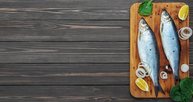 Peixes de arenque atlântico em conserva em uma tábua de corte ao lado de especiarias e limão
