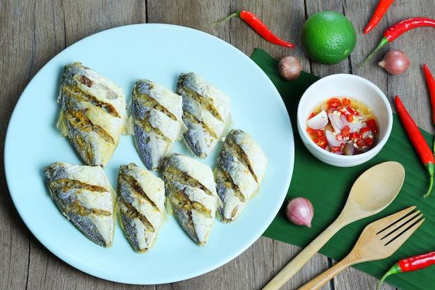 Peixes de mar fritado no molho da placa e de peixes com o picante na tabela do alimento.