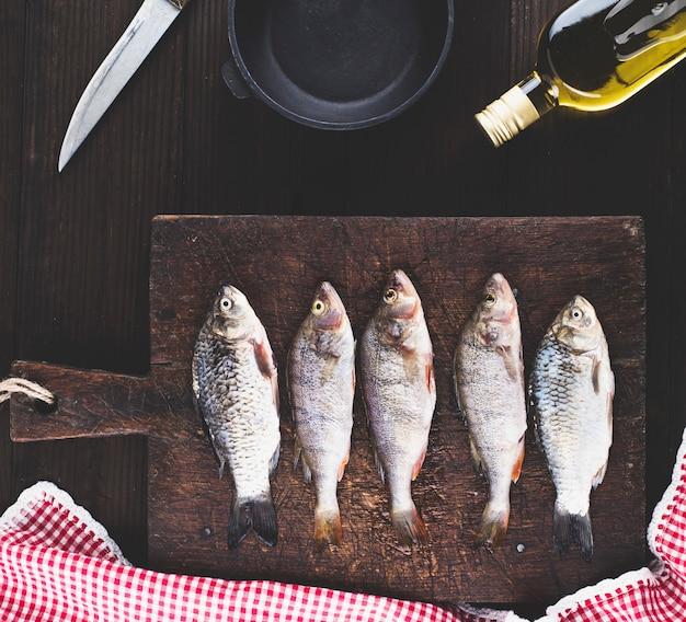 Peixes do rio purificado da balança na placa de madeira marrom
