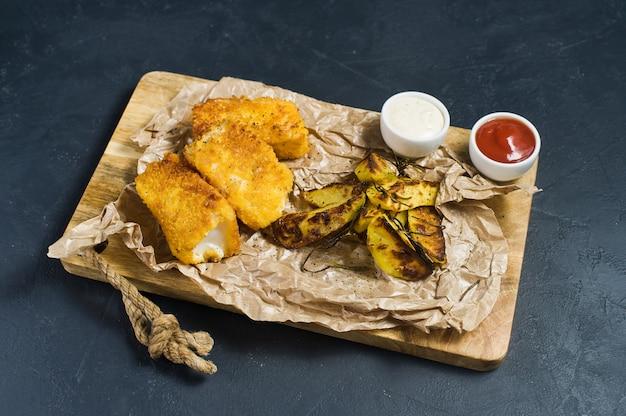 Peixes e batatas fritas tradicionais ingleses em uma placa de desbastamento de madeira.