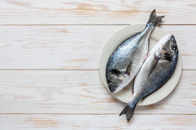 Peixes frescos do dorado no prato branco na tabela branca.