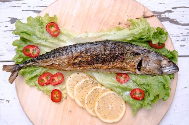 Peixes fritados com fatias do limão na salada verde da alface e na paprika vermelha. peixe inteiro assado de cavala servido na chapa de madeira com legumes