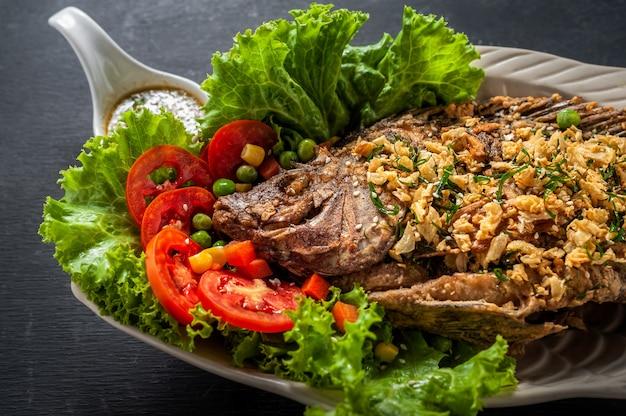 Peixes fritados com o vegetal no prato branco. vista do topo