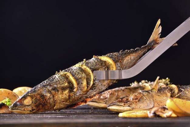 Peixes grelhados com vários legumes na grelha