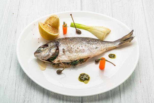 Peixes grelhados na bandeja isolada no branco. vista superior do dorado assado inteiro
