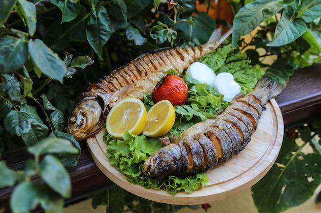 Peixes grelhados na tábua de madeira alface tomate cebola limão