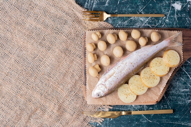 Peixes inteiros crus com azeitonas e rodelas de batata cozida na placa de madeira.