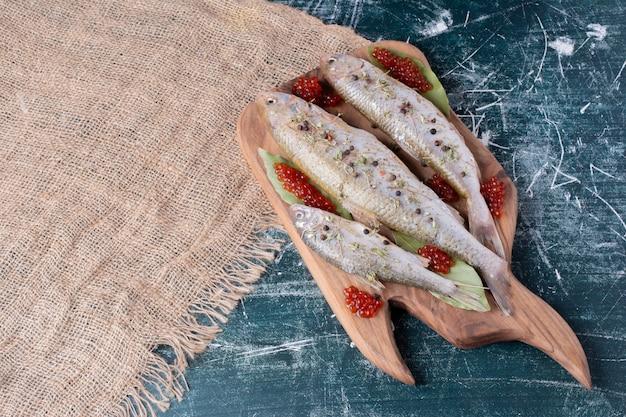 Peixes inteiros crus com caviar vermelho na placa de madeira.