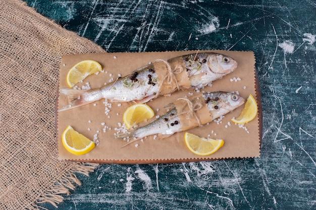 Peixes inteiros crus com rodelas de limão, grãos de pimenta e sal na placa de madeira.