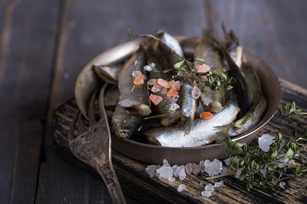 Peixes pequenos de água fria do mar fresco, como cheiravam, sardinha, anchovas em um fundo simples com espinafre fresco, rodelas de limão, legumes para o conceito de nutrição natural saudável e correta. vista do topo