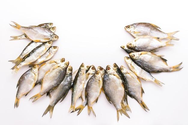Peixes secos dispostos em um semicírculo em uma superfície branca.
