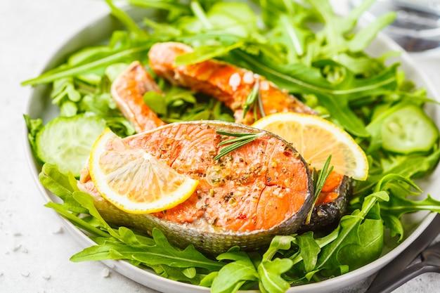 Peixes vermelhos fritados com salada da rúcula e do pepino na placa branca.