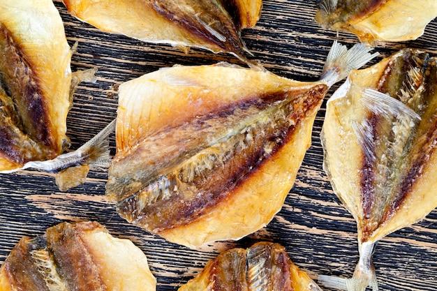 Peixinhos secos e abatidos em uma mesa de madeira