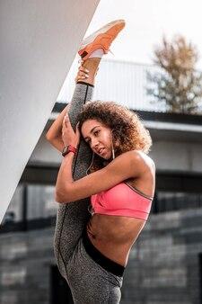 Pela dor. mulher bonita séria segurando a perna dela enquanto faz um exercício de alongamento