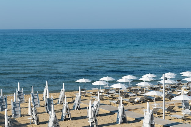 Pela manhã guarda-sóis na praia de lido di san pietro in bevagna perto de manduria