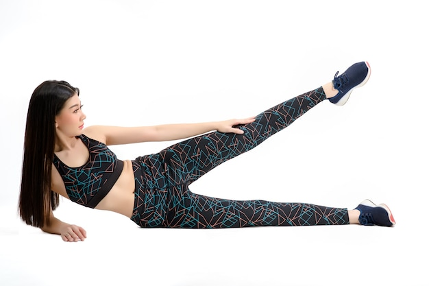 Pele bronzeada. menina asiática fitness em calças de spandex pretas sexy cute sport sutiã de exercício aquecimento. praticar exercícios para os quadris e coxas. por fundo branco isolado.