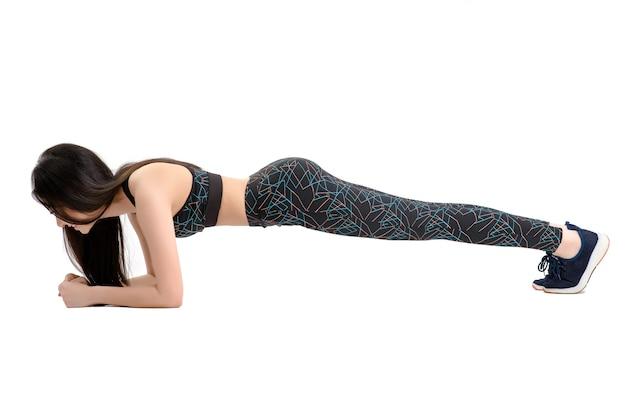 Pele bronzeada. menina asiática fitness em calças de spandex pretas sexy cute sport sutiã de exercício aquecimento. treino de fitness. por fundo branco isolado.