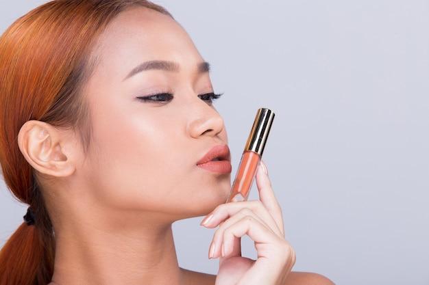 Pele bronzeada moda jovem mulher asiática modelo presente mostrando cosméticos, maquiagem, produtos, embalagem, espaço vazio, cópia, palma, mão, virar lateral, retrovisor, ombro aberto, topless, iluminação de estúdio, publicidade