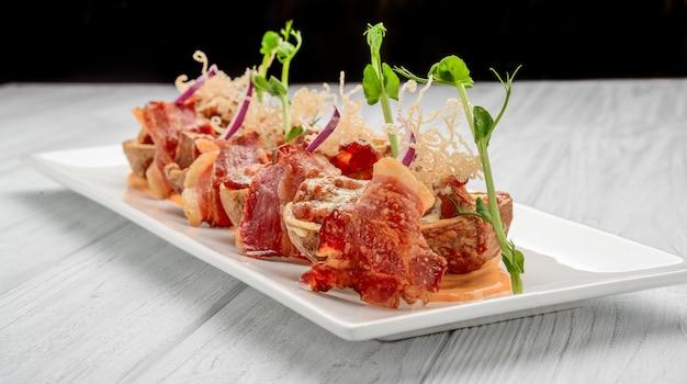 Pele de batata com bacon e queijo, molho de tomate