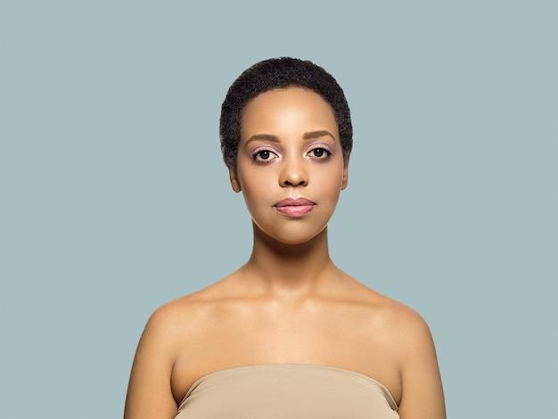 Pele de cabelo saudável de mulher de beleza de pele negra perto bela modelo afro-americana. em cinza.